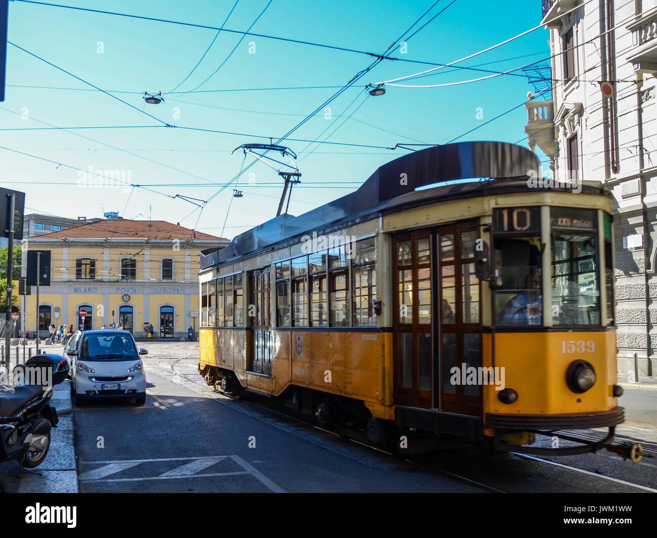A traditional 1930s tram in Milan, Italy taken at Bohemian Navigli district passing Porta Genova station - Stock Image