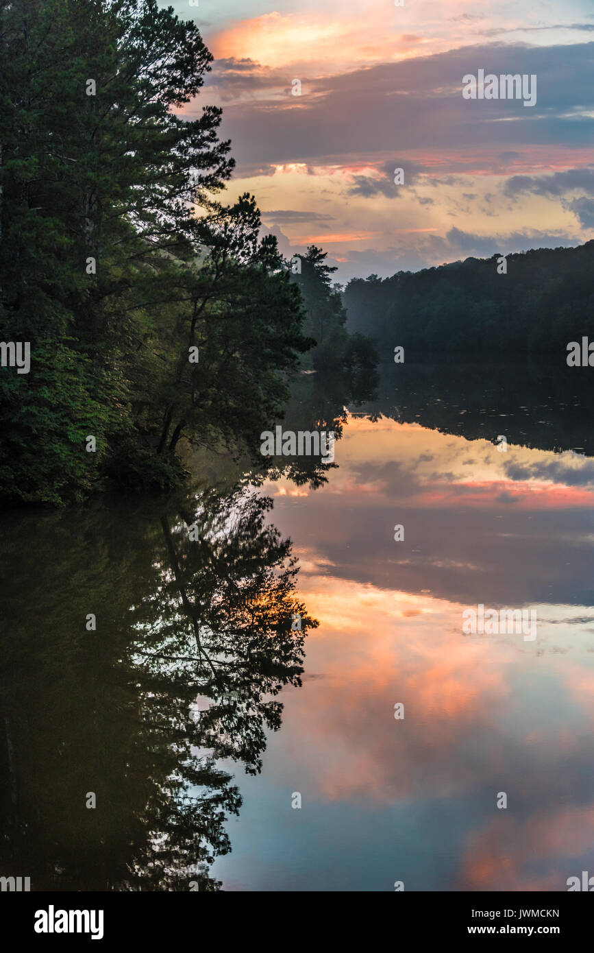 A colorful sunset sky reflects in the still water of Stone Mountain Lake at Stone Mountain Park in Atlanta, Georgia, USA. - Stock Image