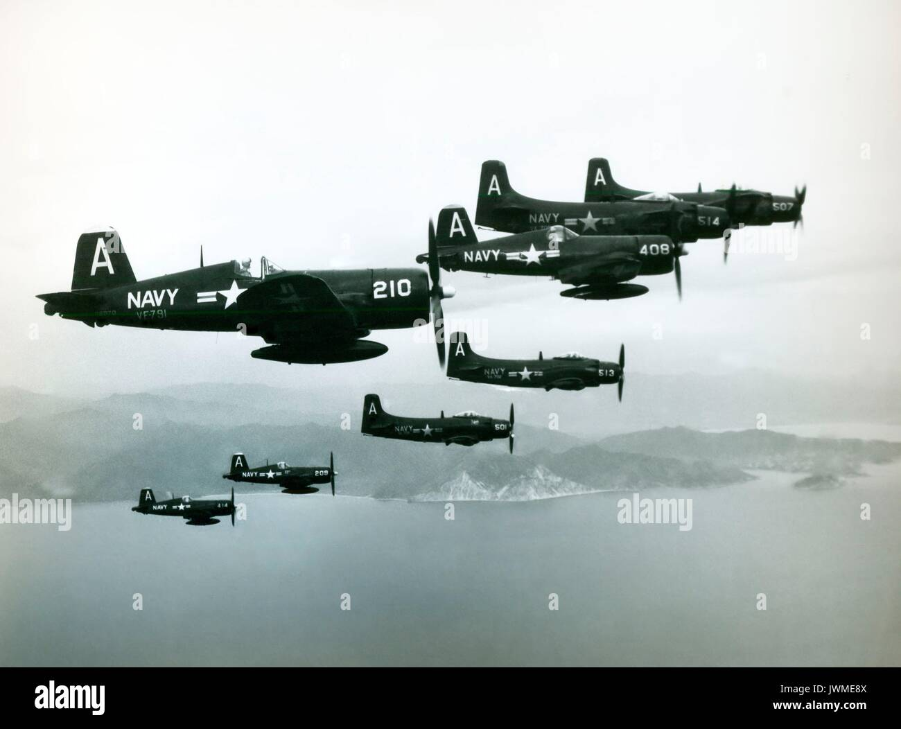 U.S. Navy Douglas A-1 Skyraiders and Vought F4U Corsair aircraft from the USS Antietam air group fly in close formation as they fly combat missions over Korea during the Korean War in 1952. - Stock Image
