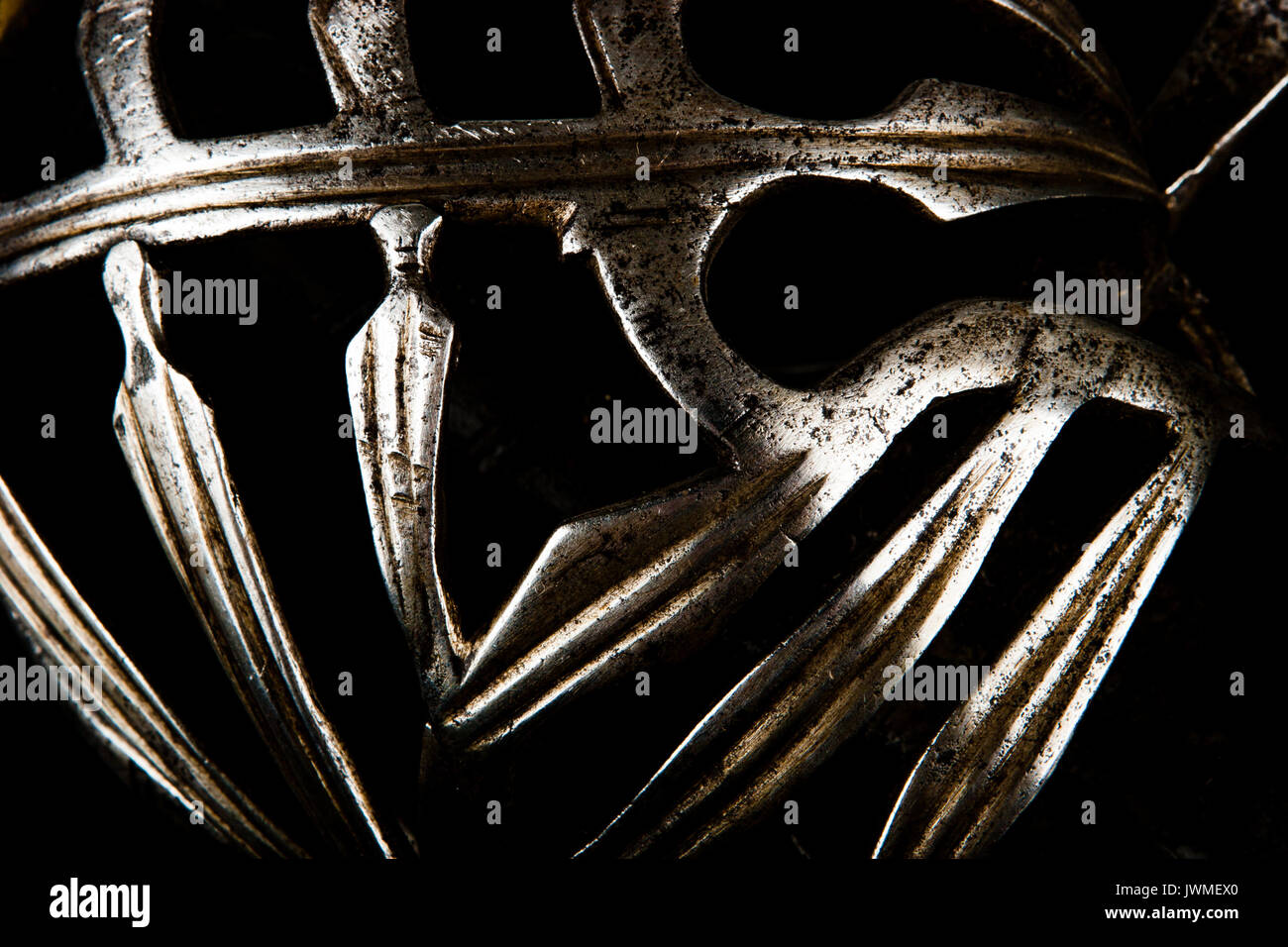 High contrast close-up image of antique Italian sword hilt components against a black background - Stock Image