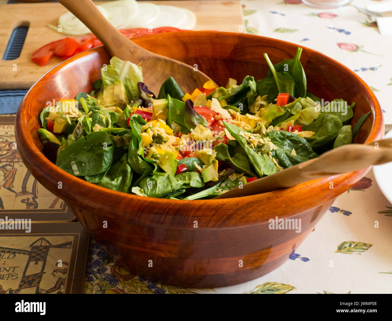A wooden bowl with spinach mixed greens salad - Stock Image