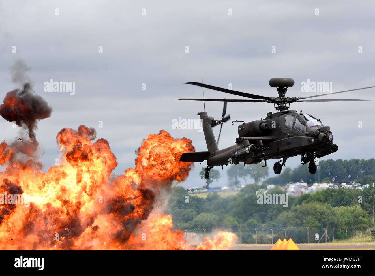 British Army Agusta Westland AH-64 Apache AH1 attack helicopter with exploding pyrotechnics at an airshow. Space for copy - Stock Image