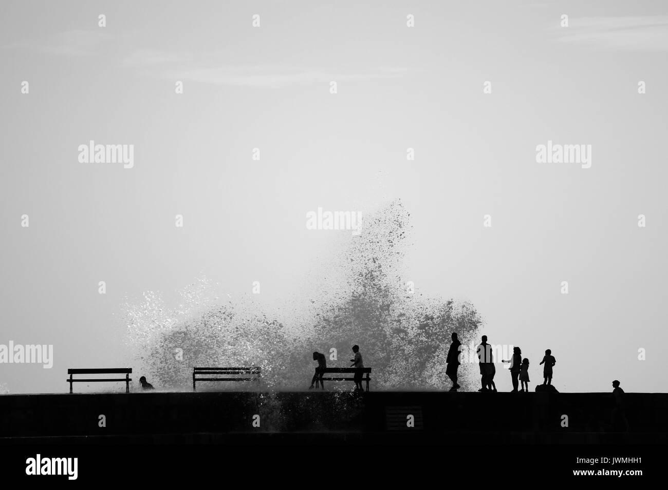People silhouettes on the brakewater, big waves, water splashing, Porporela in Dubrovnik, Croatia Stock Photo