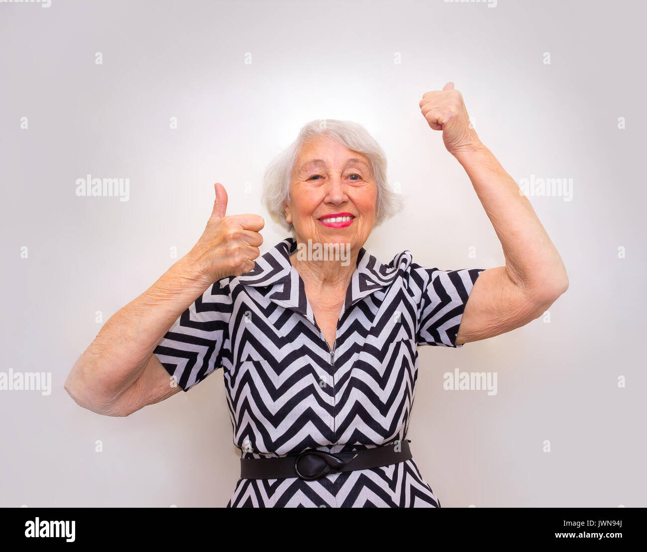 The portrait of a cheerful senior woman gesturing victory over pink - Stock Image