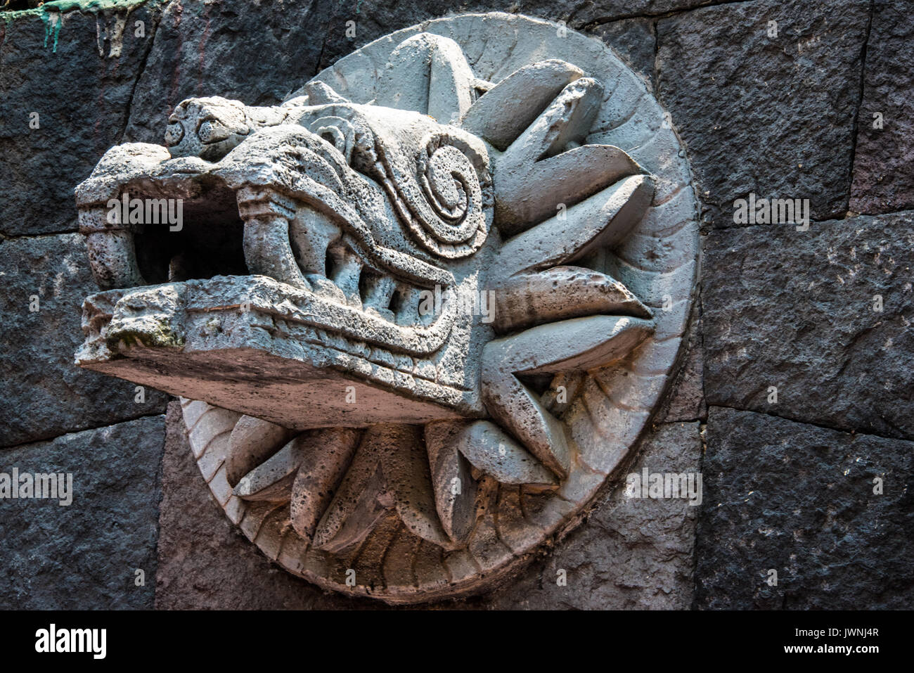 Old stone carving of quetzalcoatl the ancient feathered serpent