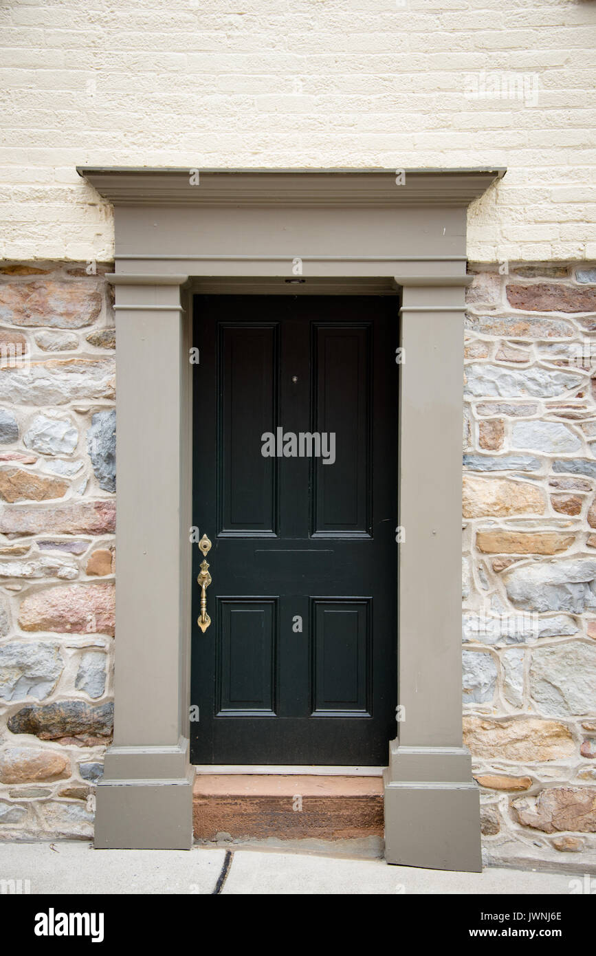 Old Black Painted Wooden Door With Brass Handle In Colonial Architecture  With A Plain Carved Stone Surround Set Into A Natural Rock Wall Changing To  B