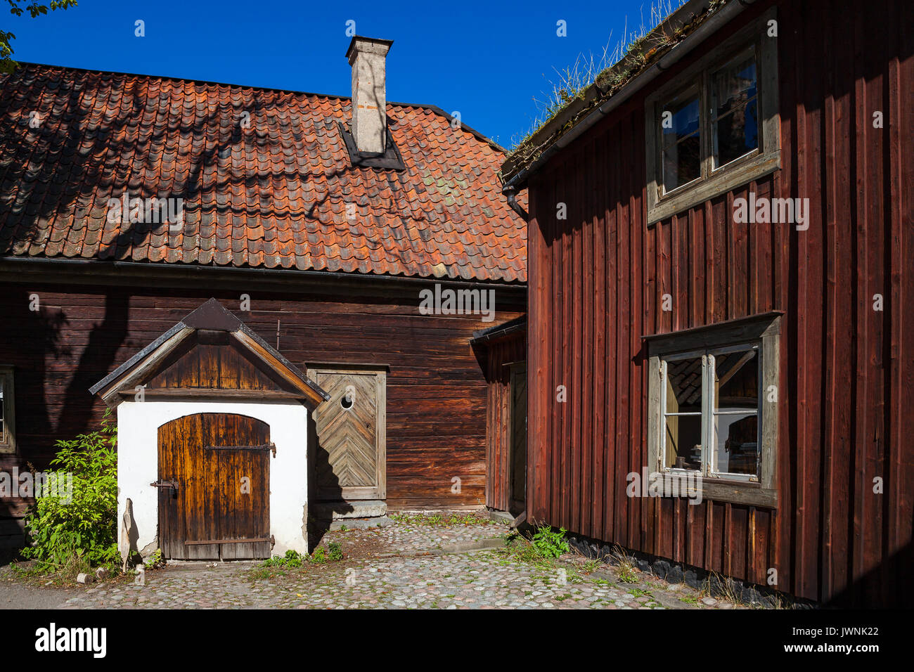 Traditional red wooden dwelling and farm in Skansen museum. Sweden - Stock Image