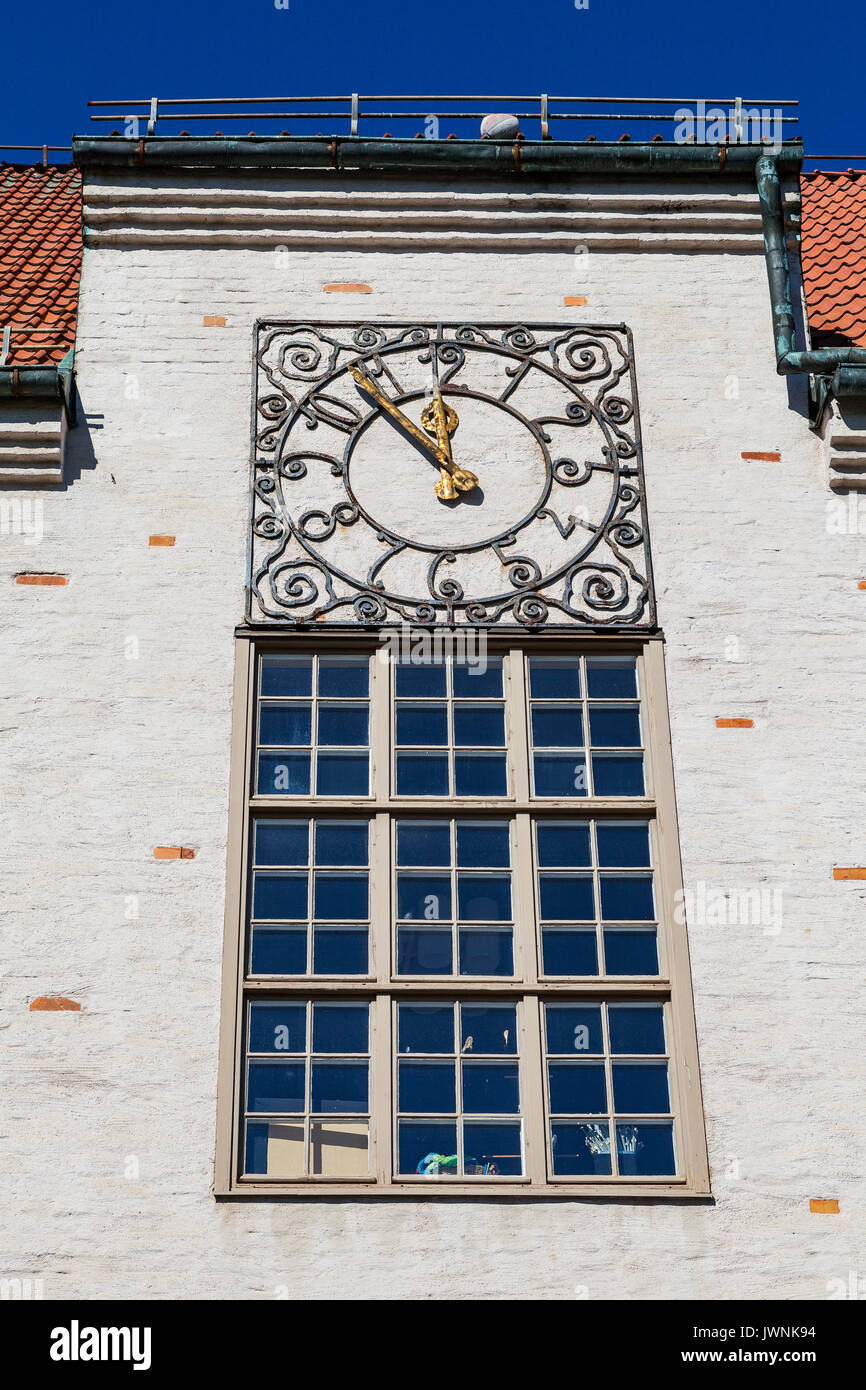 Ancient clock with golden arrows on old City hall wall. Hedemora, Sweden. - Stock Image