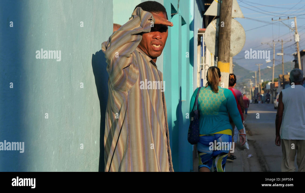 Black man shading his eyes from sun with hand. Trinidad, Cuba - Stock Image
