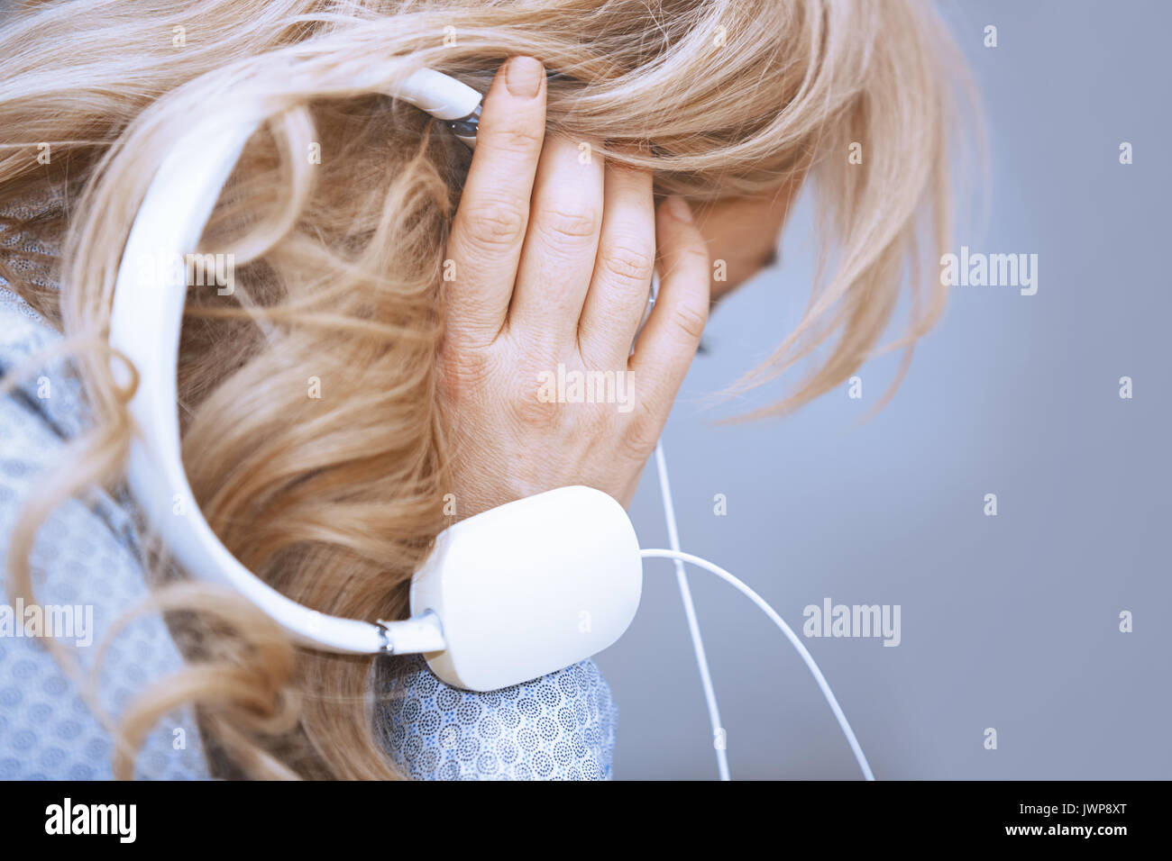 Blond woman listening music via headphones - Stock Image
