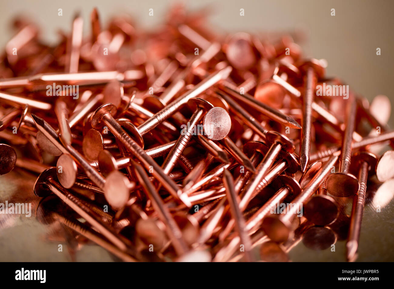 Copper Nails on Galvanized Steel Background With Shallow Focus - Stock Image