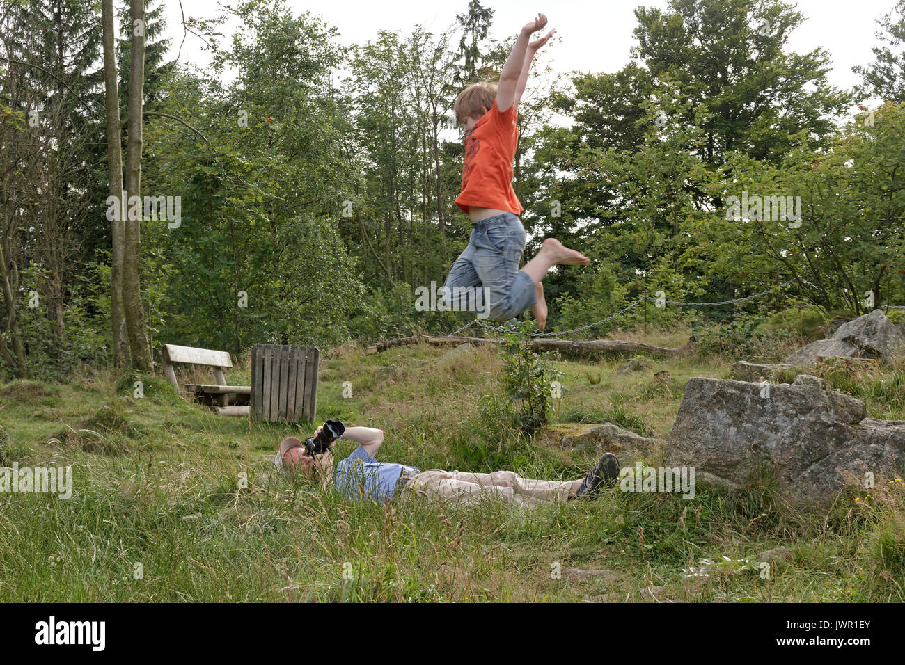 man taking photo of jumping boy - Stock Image