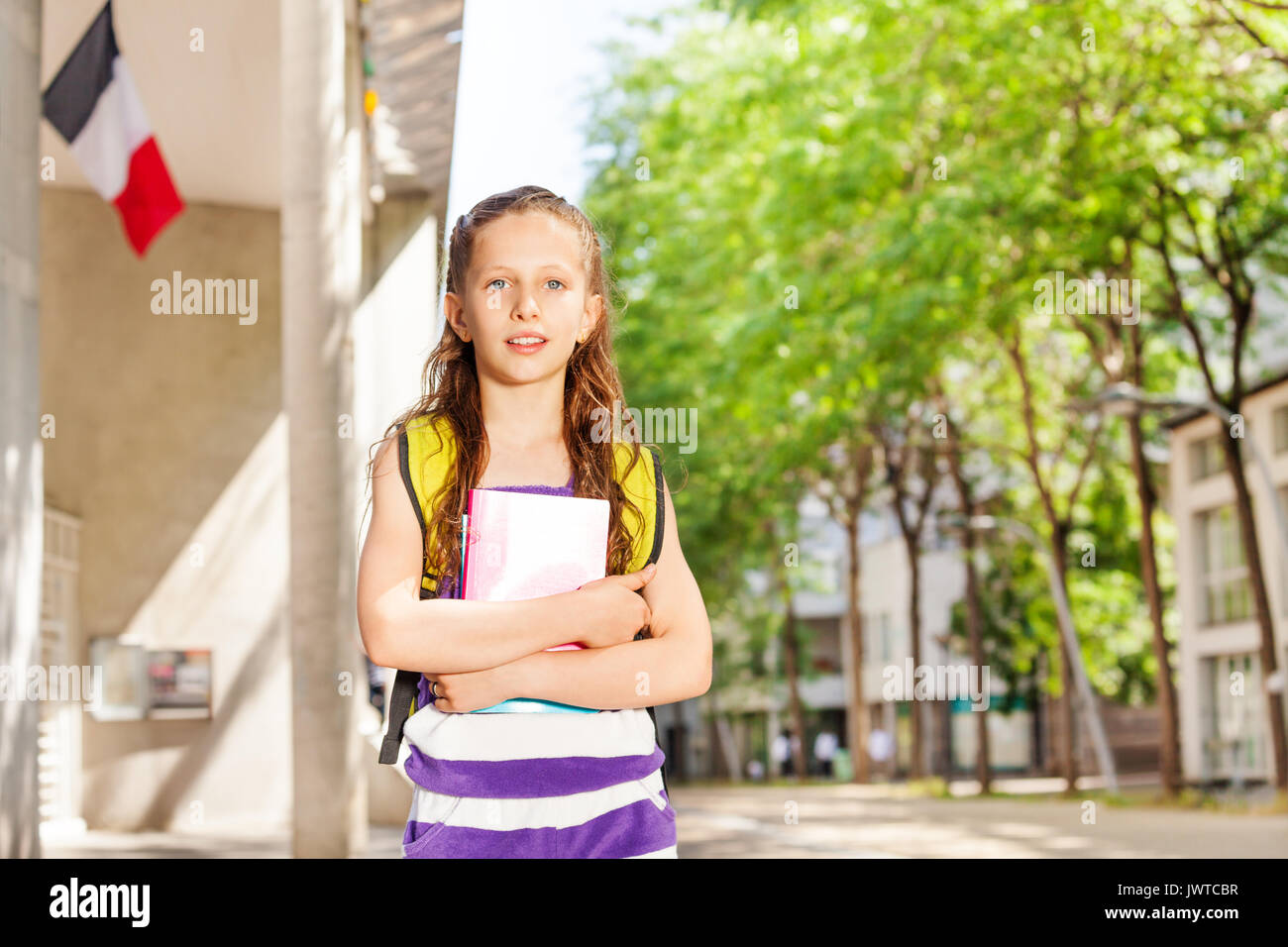Close portrait of a girl holds textbook near the public school  with French flag - Stock Image