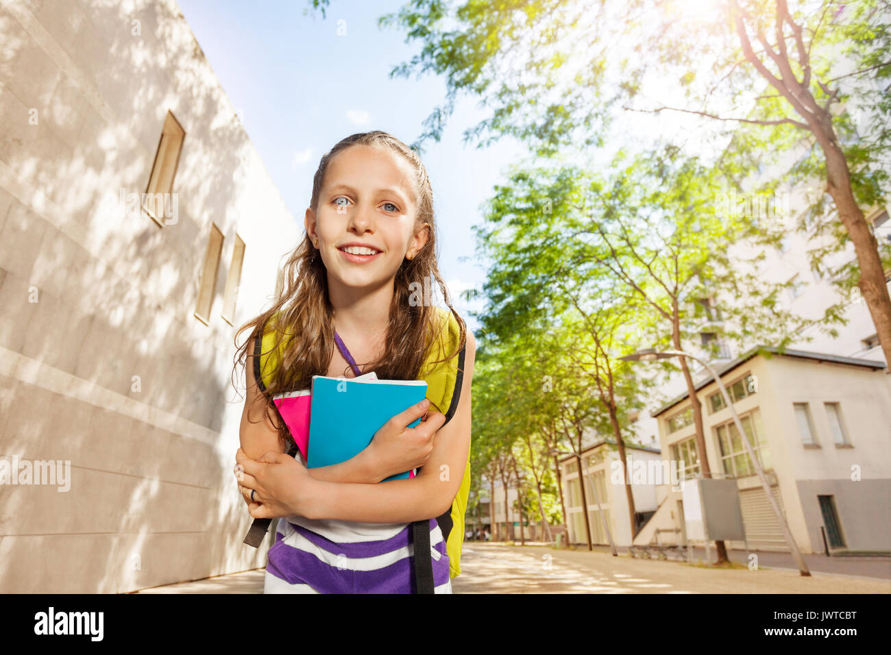 Close nice portrait of a Caucasian girl with textbooks near school - Stock Image