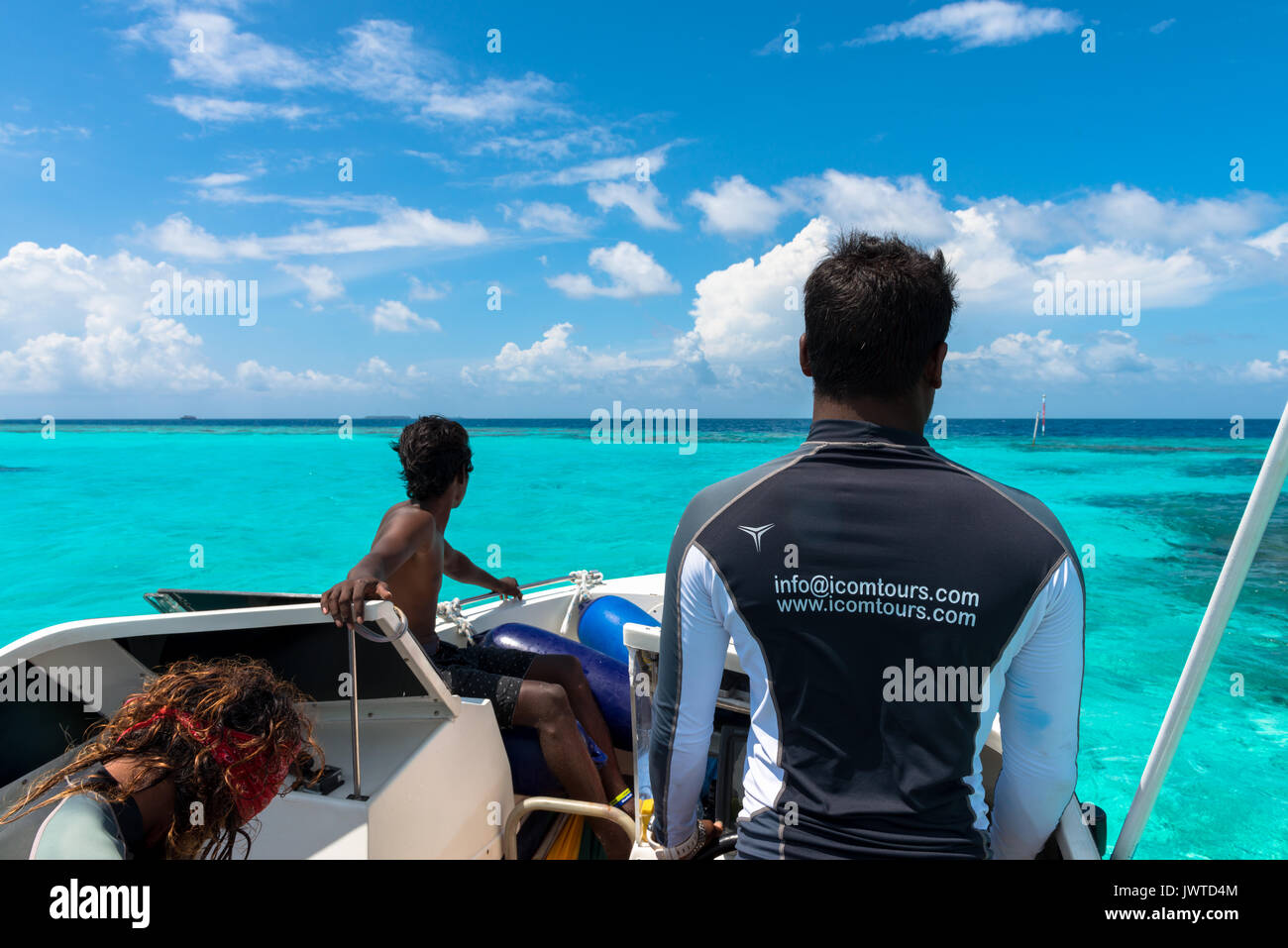 MAAFUSHI, MALDIVES - FEBRUARY 29, 2016: Wide angle picture of three local Maldives men guiding tourists over the turquoise water in Maldives. - Stock Image