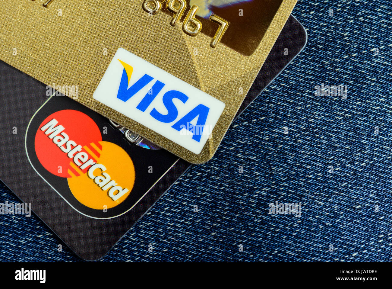 Moscowi, Russia - August 05, 2017: Visa and Mastercard credit cards over blue jeans - Stock Image