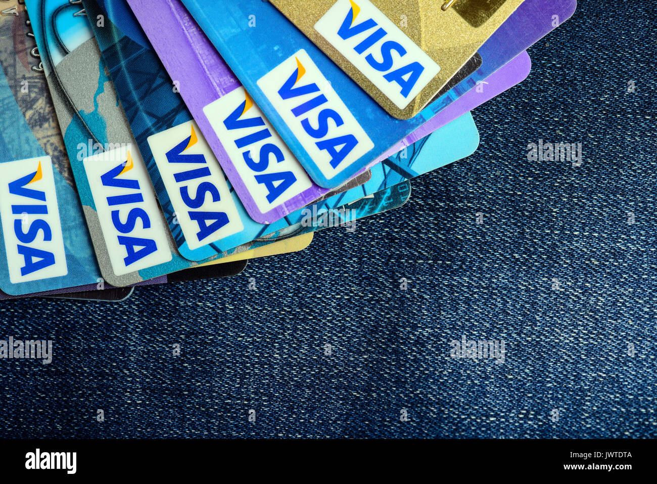 Moscowi, Russia - August 05, 2017: Visa credit cards over blue jeans - Stock Image