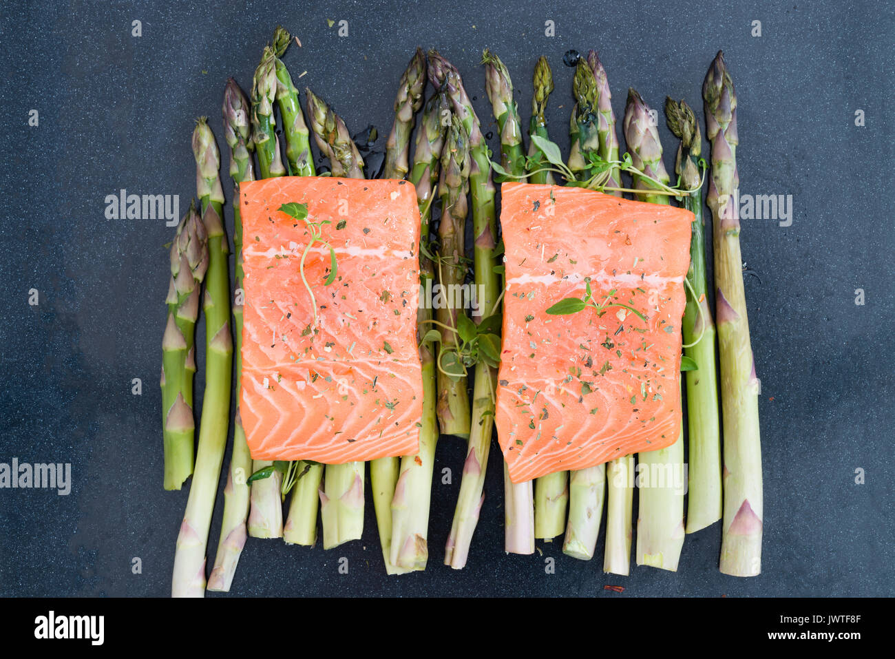 Two pieces of fillet of raw uncooked salmon on green asparagus on baking tray garnished with fresh thyme. Ingredients Stock Photo