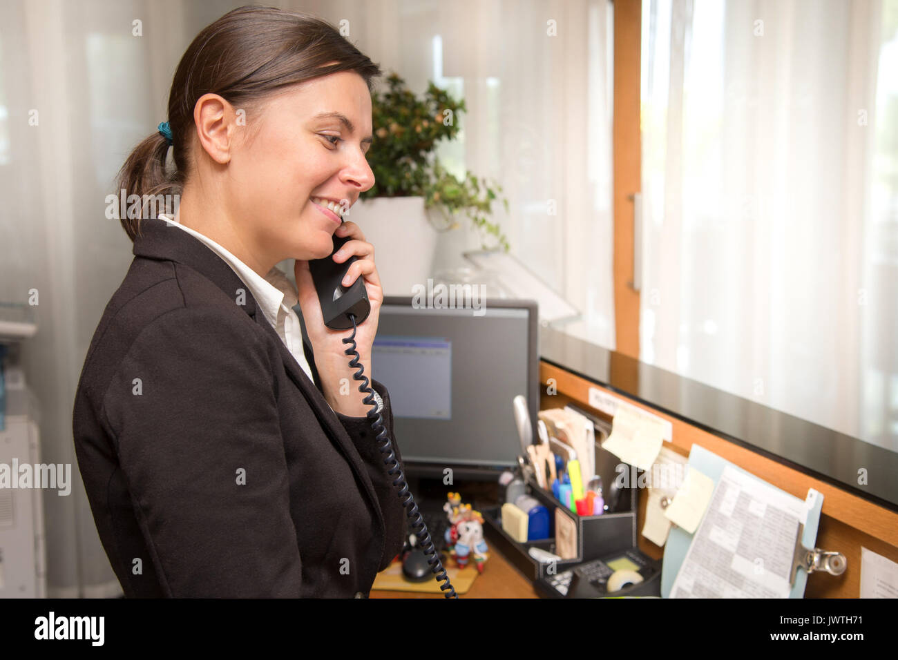 Professional receptionist answering to the phone call - Stock Image