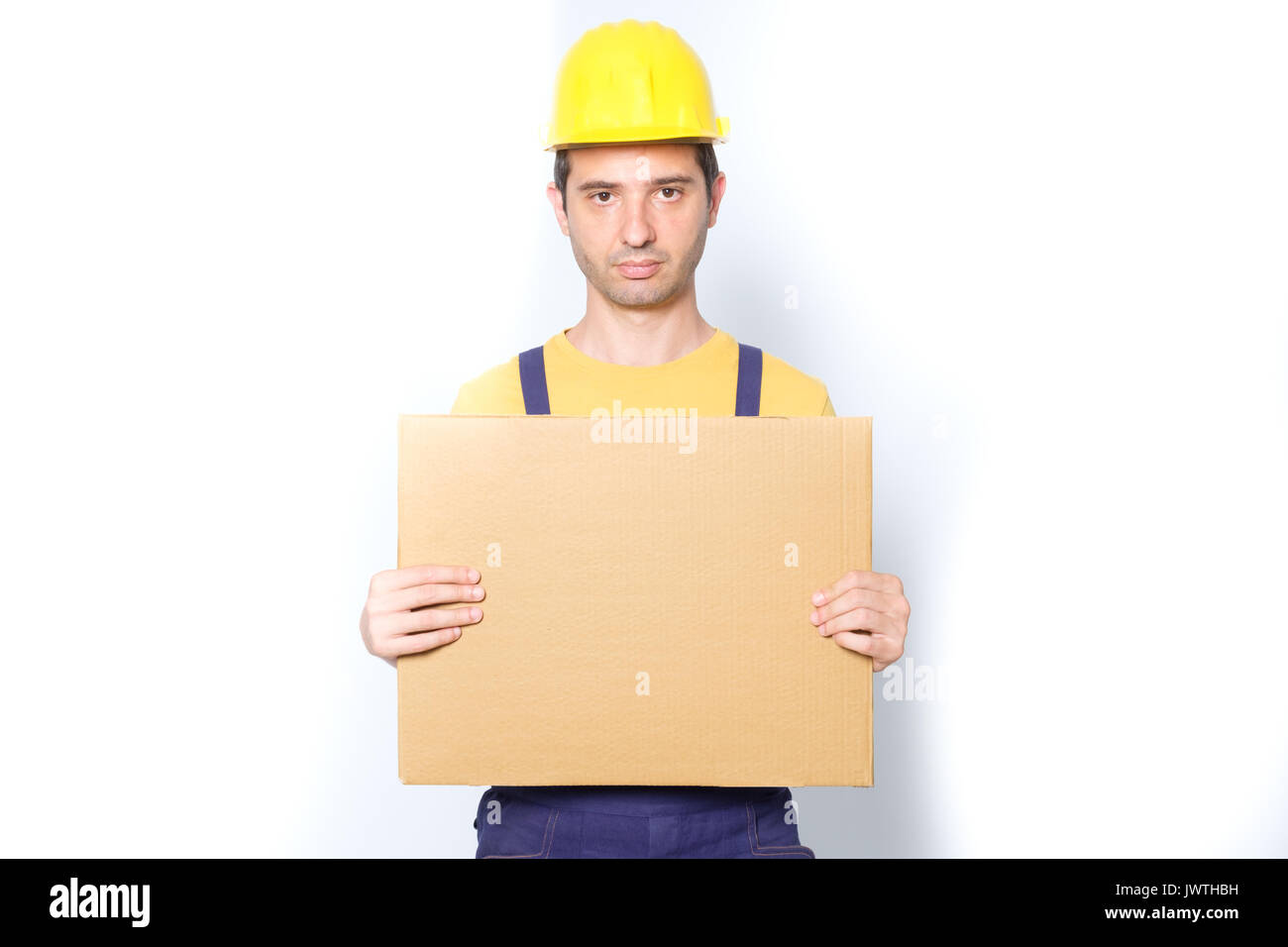 Sad worker holding a cardboard isolated on white background - Stock Image