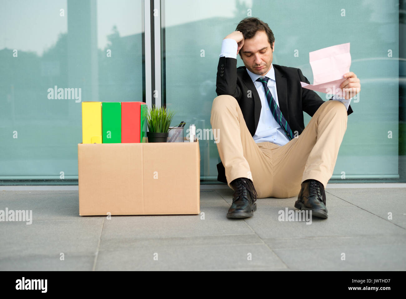 Fired businessman reading the notice of job termination outside a financial district building - Stock Image