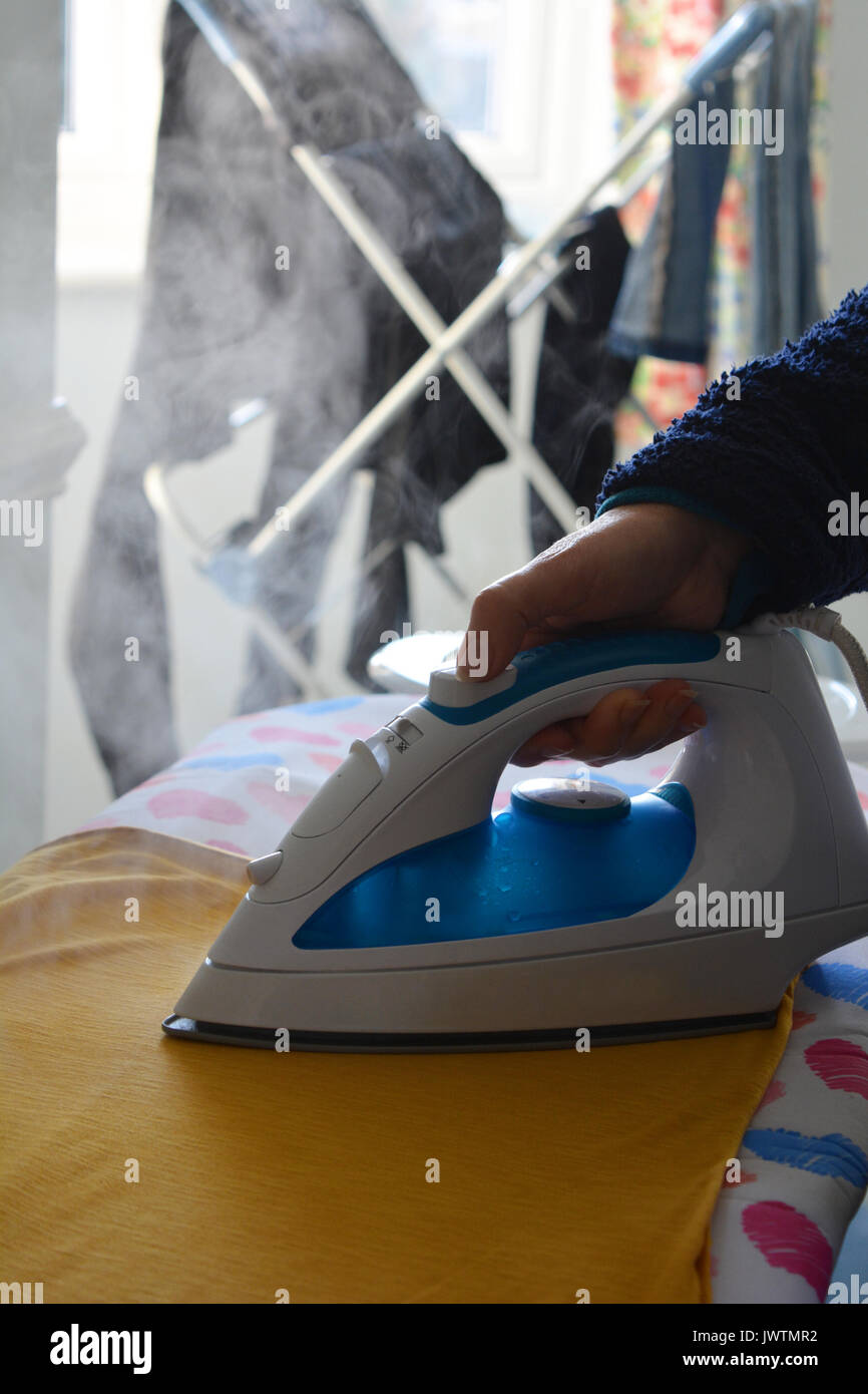 Housework. Woman doing the ironing, close-up of iron and ironing board - Stock Image