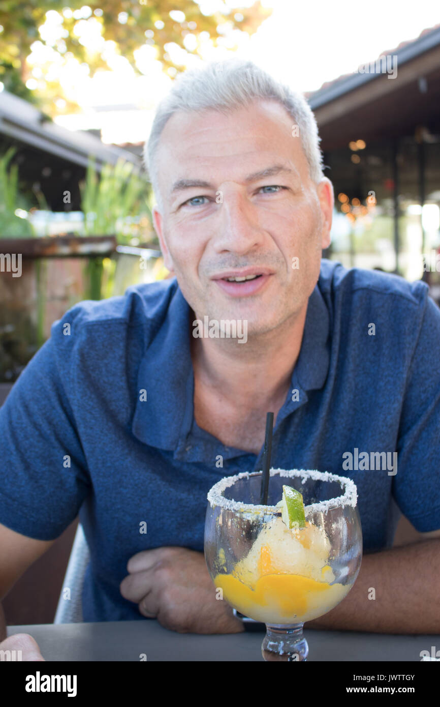 Youthful middle aged man smiling, talking and sitting at a table with a frozen margarita in front of him. Background blurred outdoor restaurant. - Stock Image