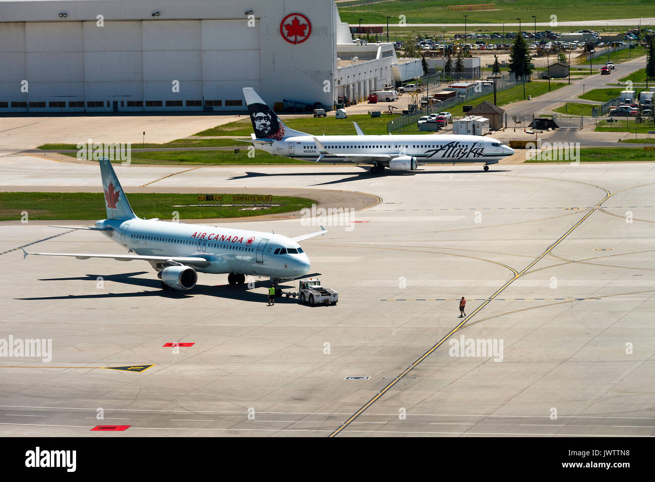 Air Canada Airline Airbus A320-214 Airliner C-GJVT Being Towed to Stand and Alaska Airlines Boeing 737-890(w) Taxiing at Calgary  Alberta Canada - Stock Image