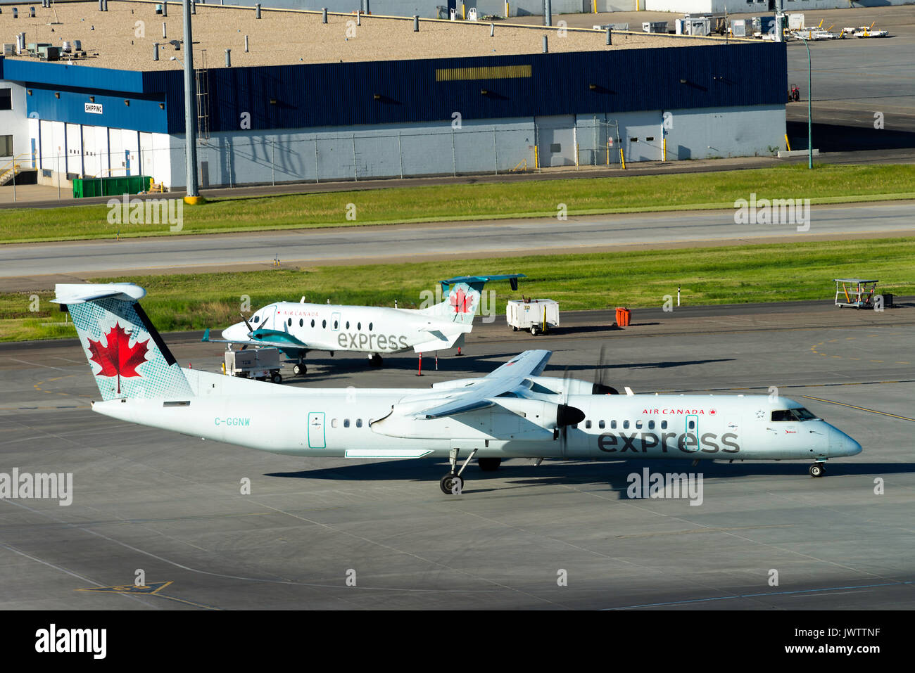 Air Canada Express Airline Bombardier Dash 8-402 Turboprop Airliner Taxiing Past Beechcraft 1900D Aircraft at Calgary Airport Alberta Canada - Stock Image