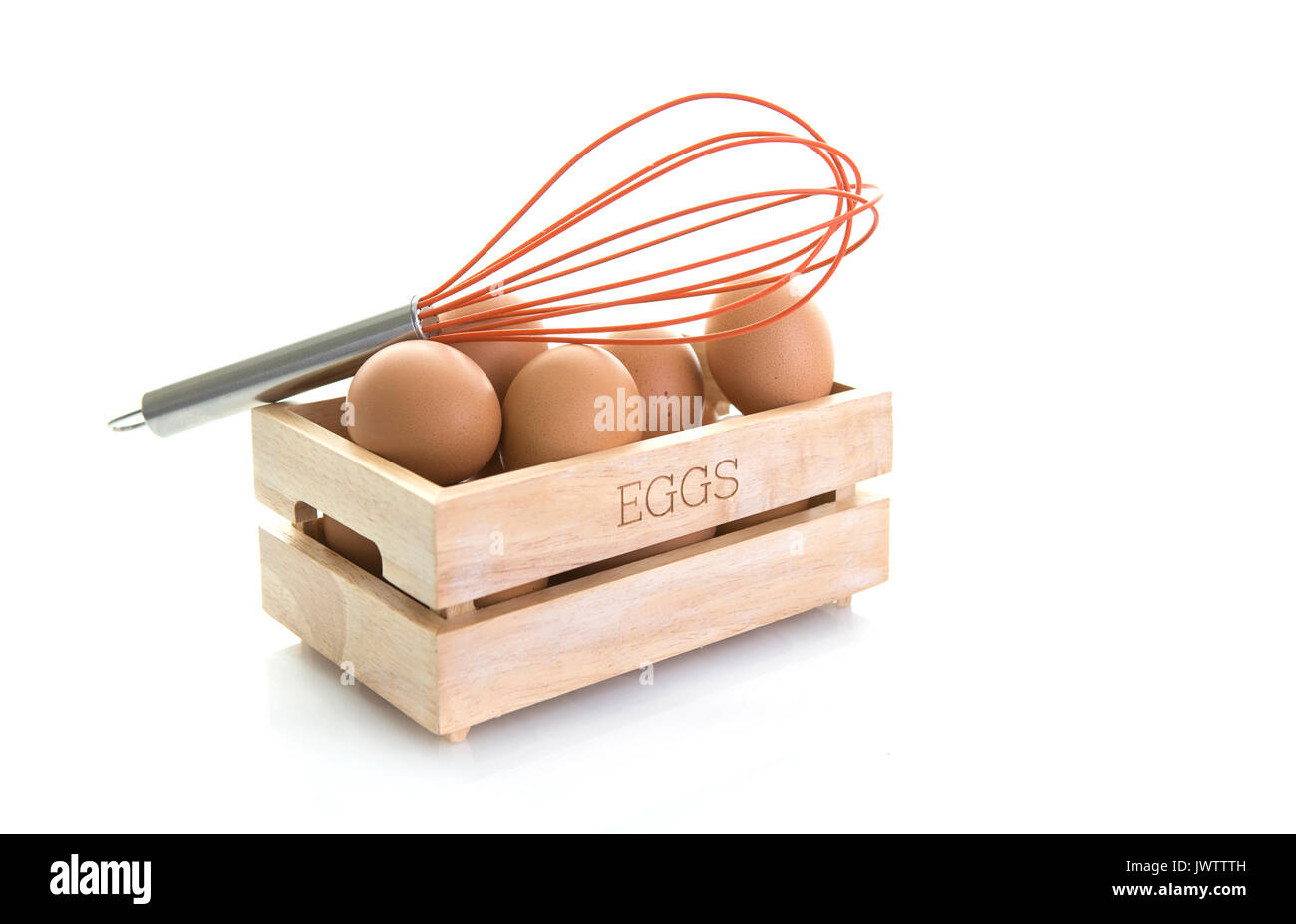 Eggs in a wooden box with Orange egg whisk on a white background Stock Photo