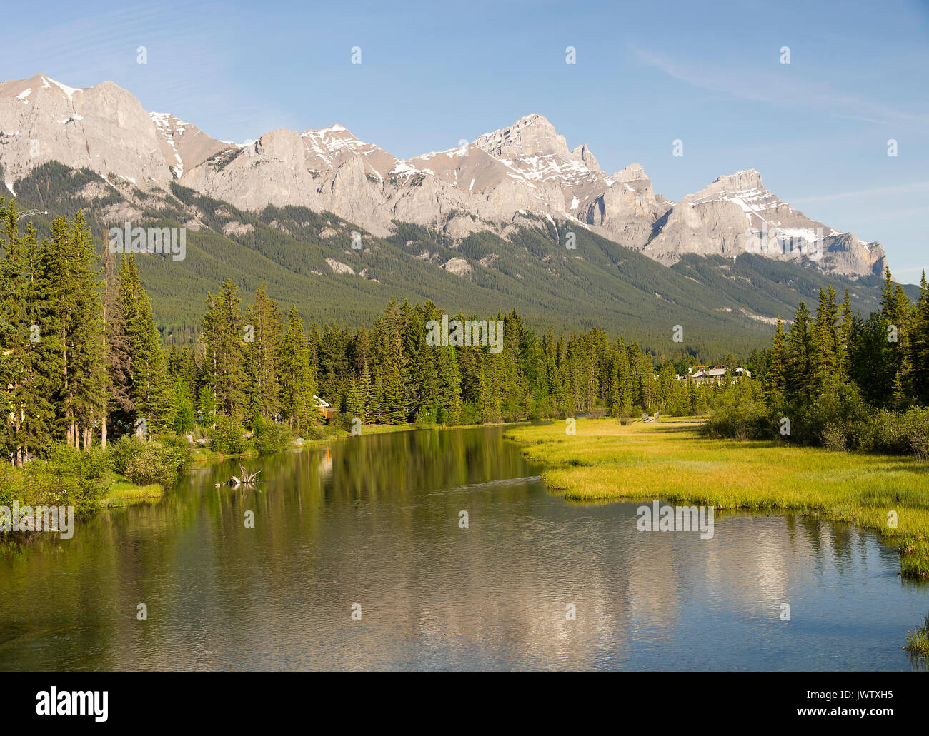 The Bow River Flowing Through Canmore in Banff National Park with Pine Forest and Rocky Mountain Range Alberta Canada - Stock Image