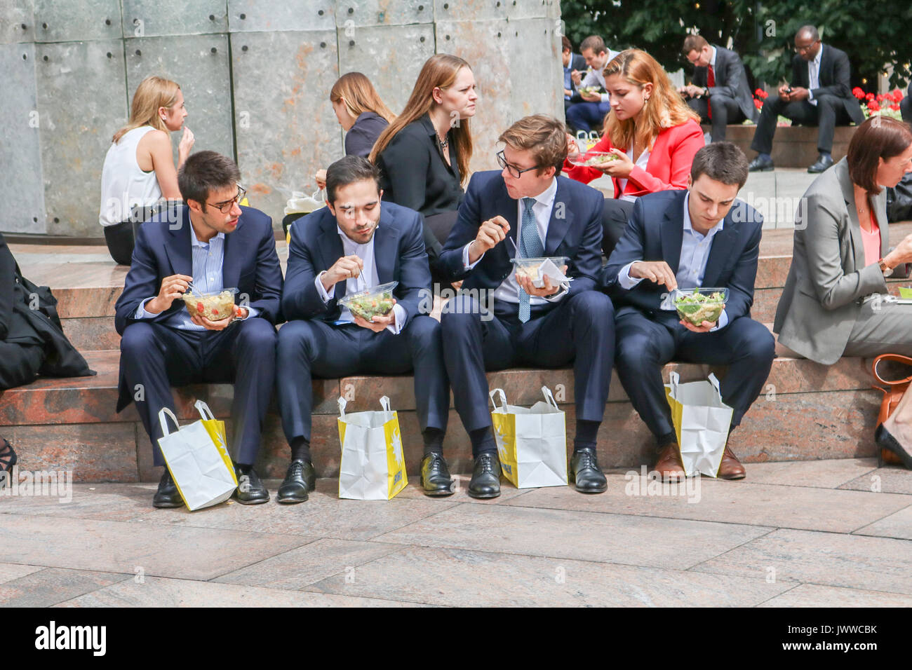 London, UK. 14th August 2017. City workers in the enjoy their lunch in the sunshine in Canary Wharf financial district Stock Photo