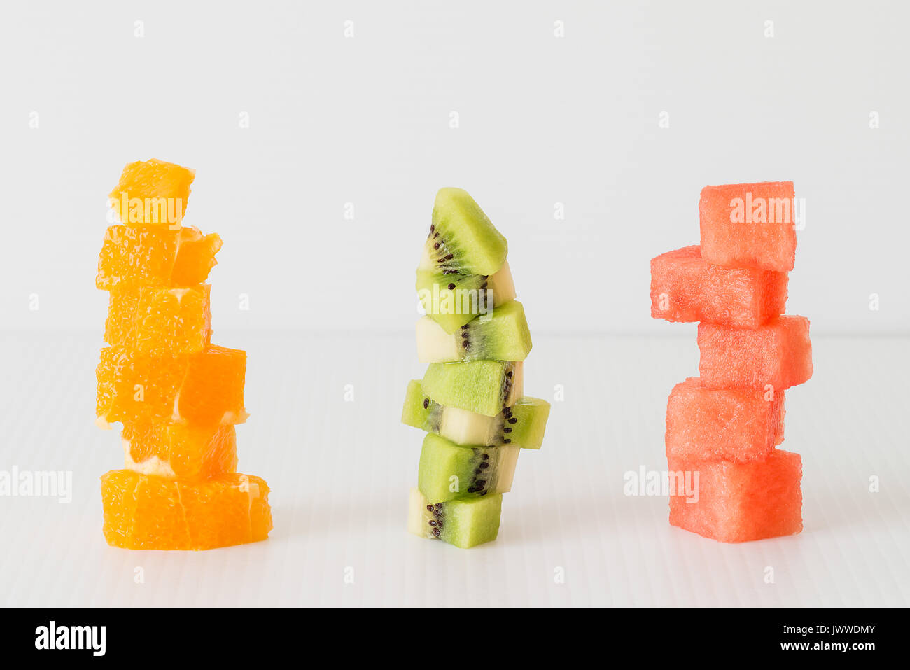 Three stacks of chopped fresh summer fruits: orange, kiwi, watermelon. Healthy snack concept. Vegetarian meal - Stock Image