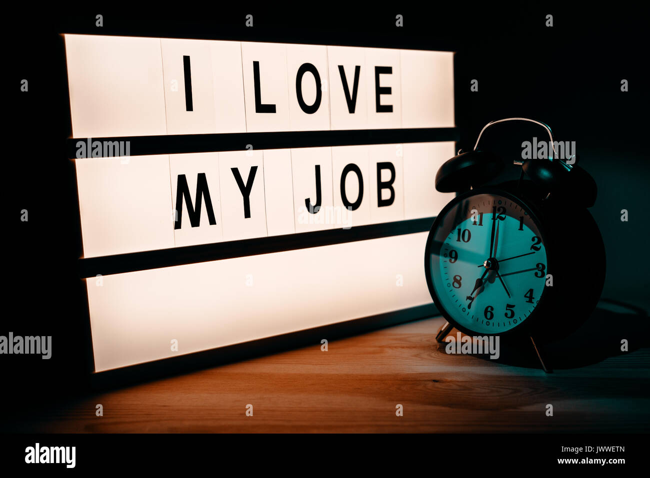 I love my job, business and occupation motivational message on lightbox in the office next to the vintage style clock - Stock Image