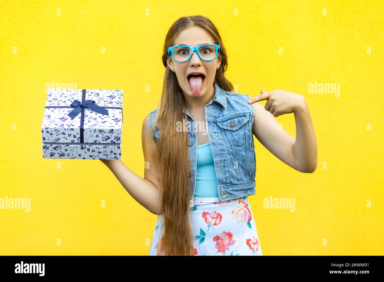 The funny blonde girl in dress and blue glasses, tongue out at the camera, pointing finger on present box, isolated over yellow background. Indoor stu - Stock Image