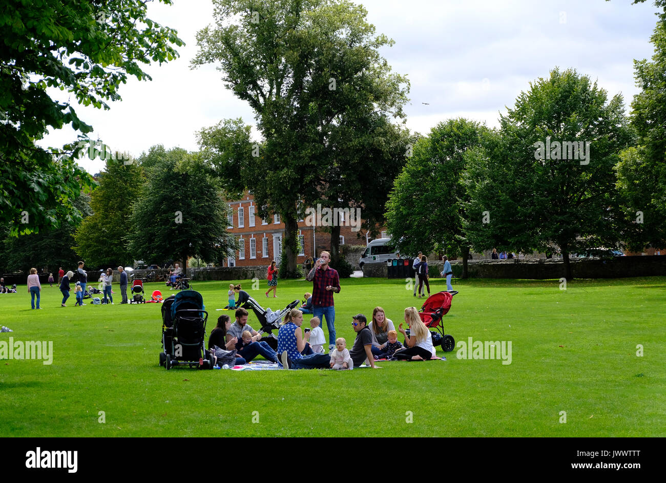 Family and friends picnicking in the grounds of Salisbury Cathedral, Wiltshire,UK - Stock Image