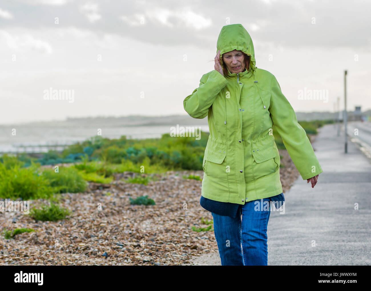 Elderly woman walking along a seafront road in cloudy wet and windy weather, keeping her ears warm. - Stock Image