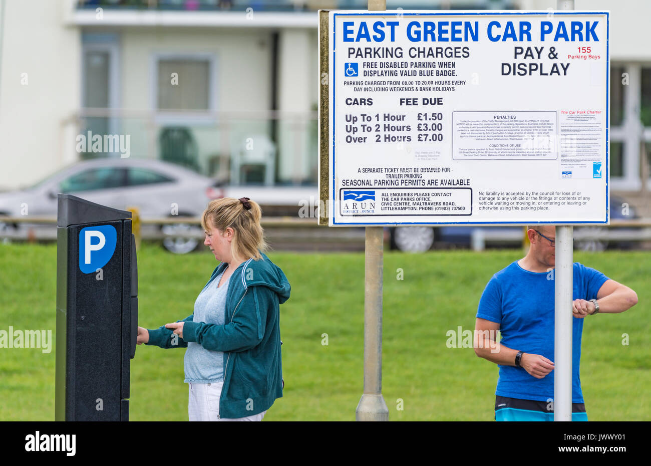 Woman putting money in a parking machine to purchase a ticket at a pay and display car park in the UK. - Stock Image