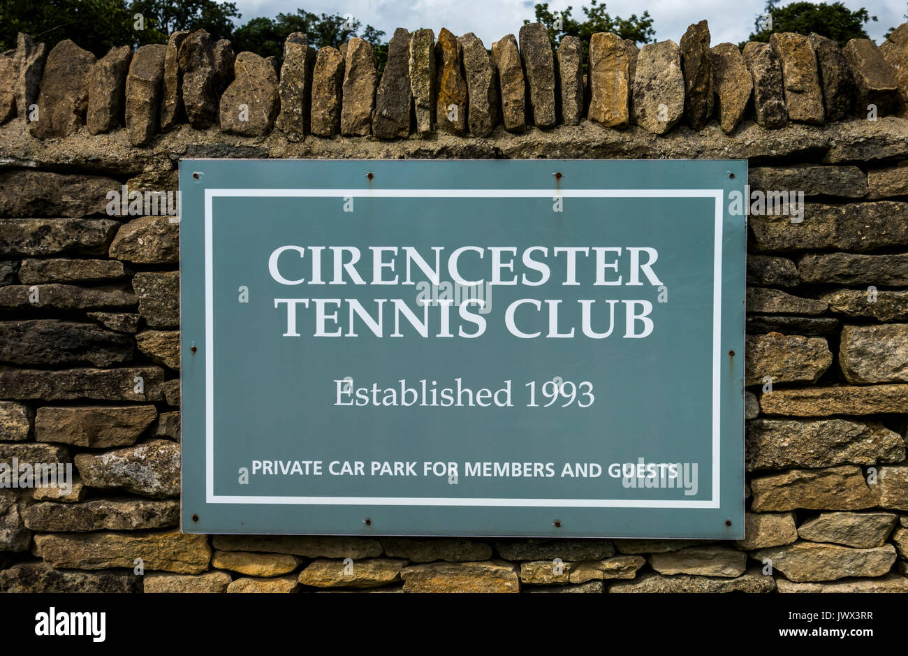 Cirencester Tennis Club sign attached to a stone wall on the Bathurst Estate. Cirencester, Gloucestershire, England, UK. - Stock Image