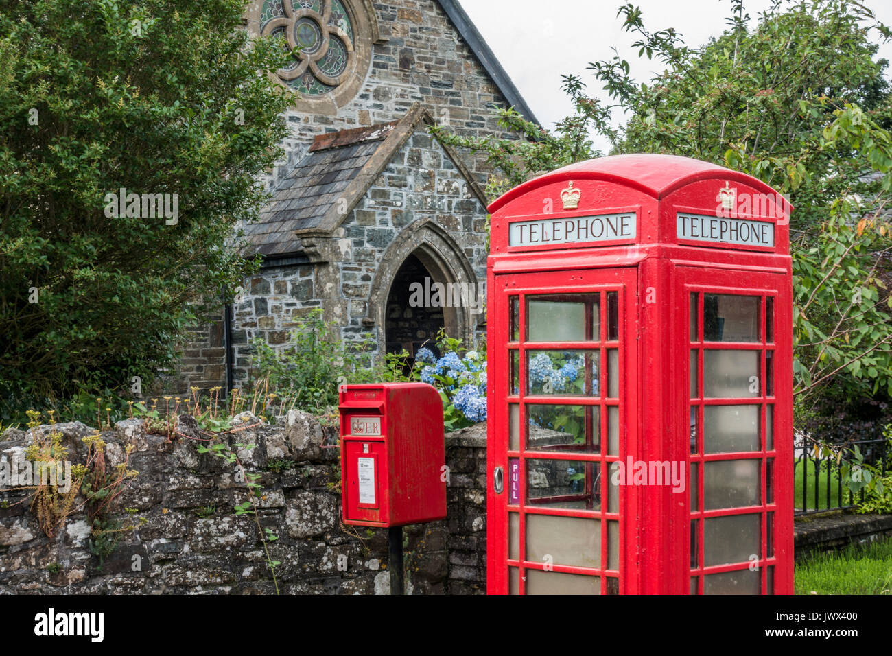 A traditional red Royal Mail postbox alongside an iconic red telephone kiosk, outside the old church, Lydford, near Okehampton, Devon, England, UK. - Stock Image