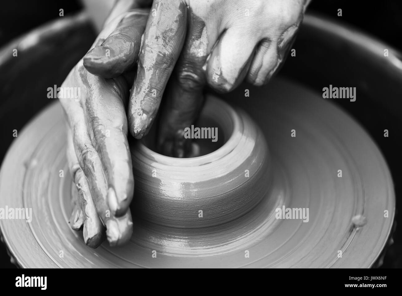 Hands of a potter. Potter making ceramic pot on the pottery wheel - Stock Image