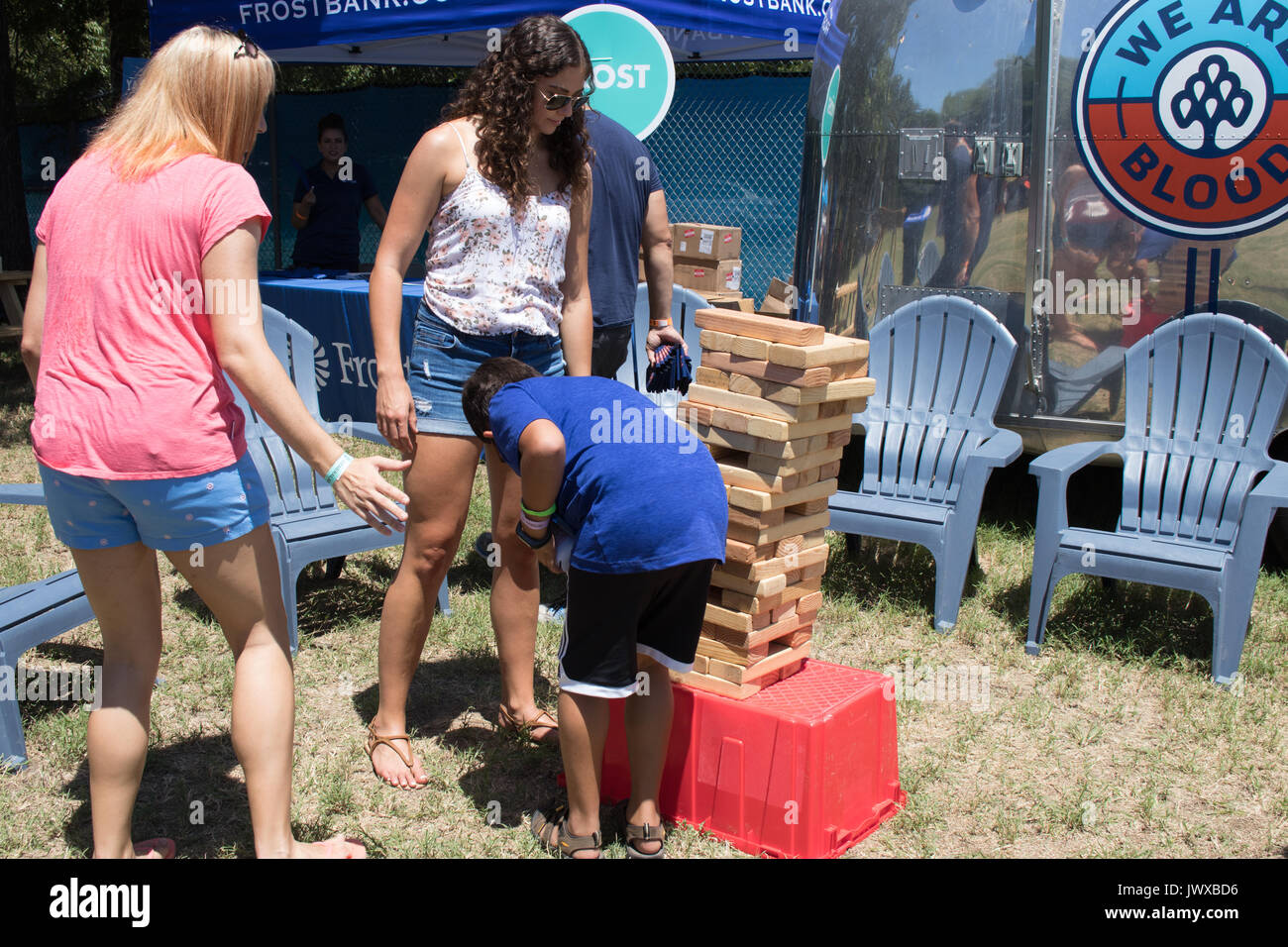 Three people playing giant Jenga game outdoors with chrome Airstream bloodmobile in background at Austin Ice Cream Festival. - Stock Image