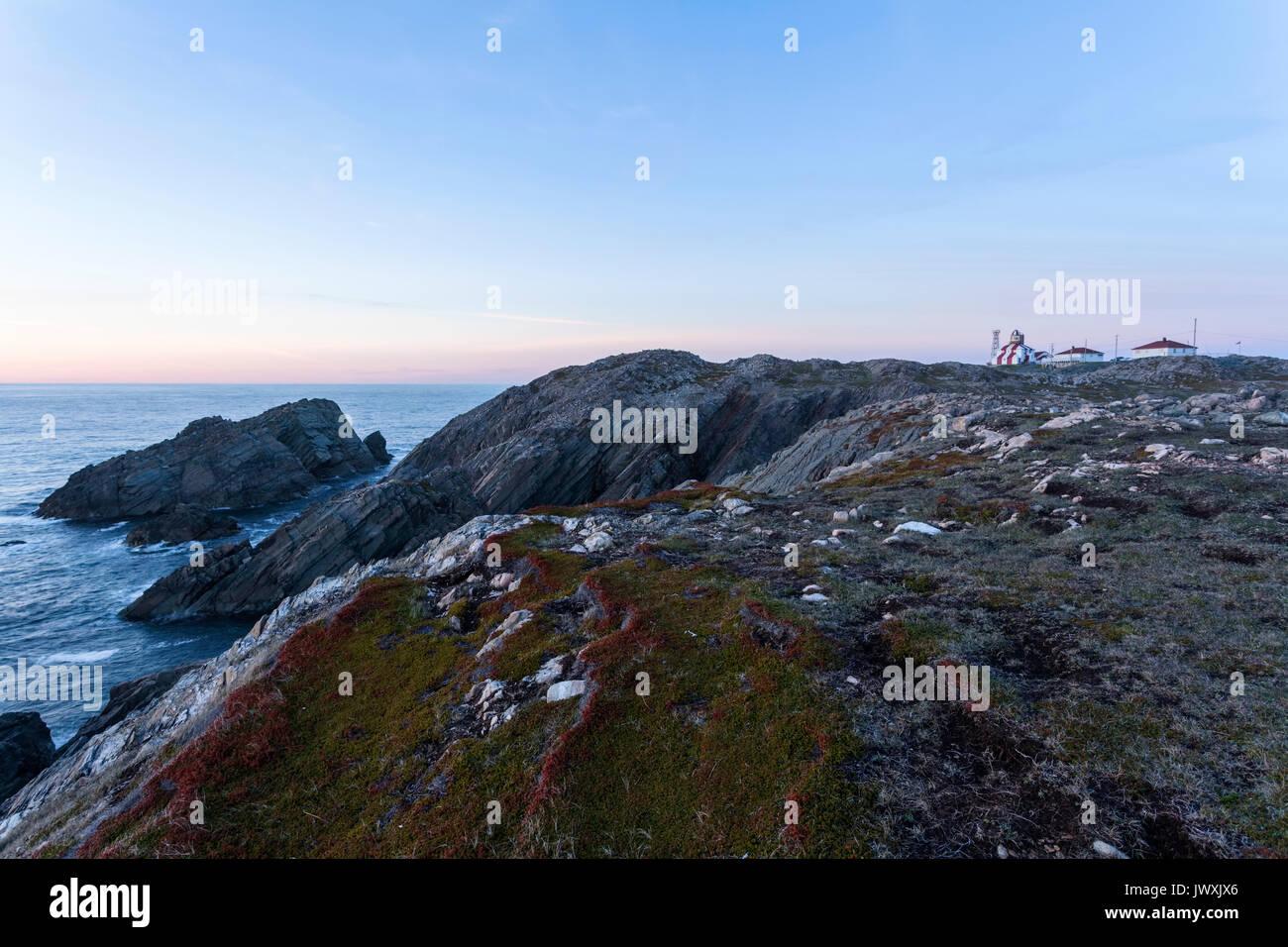 Sunset over the rocky Cape Bonavista coastline with the Cape Bonavista Lighthouse in the distance. Bonavista Peninsula, Newfoundland. - Stock Image