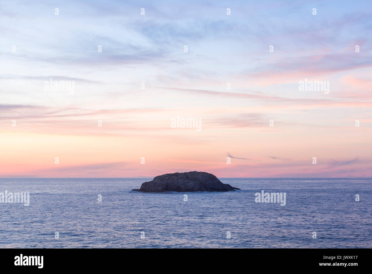 A lone rock in the Atlantic ocean at sunset brings feelings of loneliness, isolation and power in Bonavista, Newfoundland and Labrador, Canada. - Stock Image