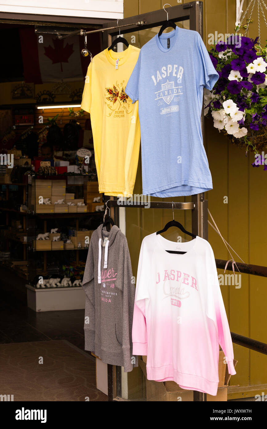 T-Shirts Hanging Up For Sale Outside a Gift and Clothes Shop in Jasper Alberta Canada - Stock Image