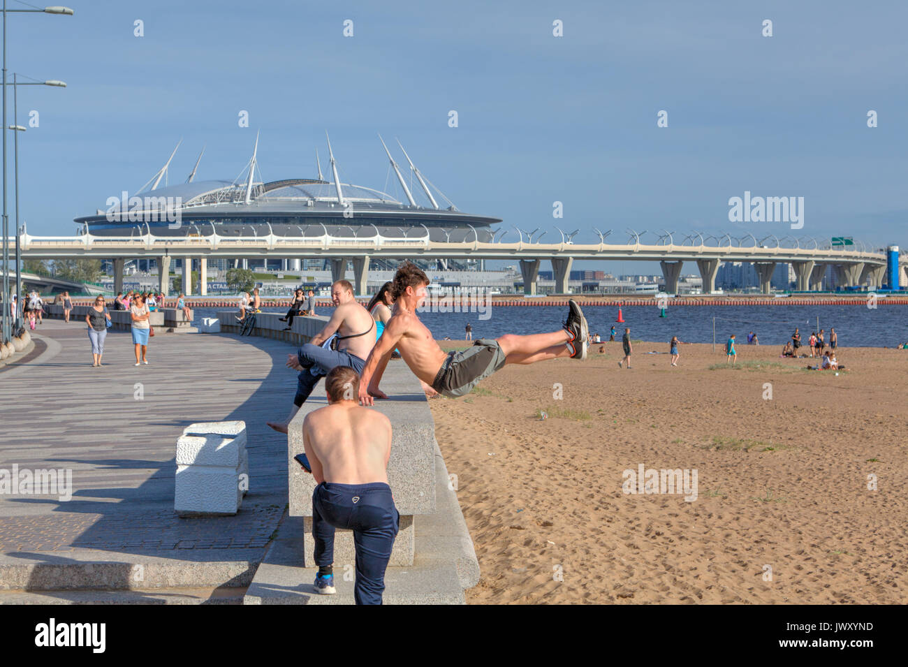St. Petersburg, Russia - August 1, 2017: Park of the 300th anniversary of St. Petersburg, young man trains parkour in beach. - Stock Image