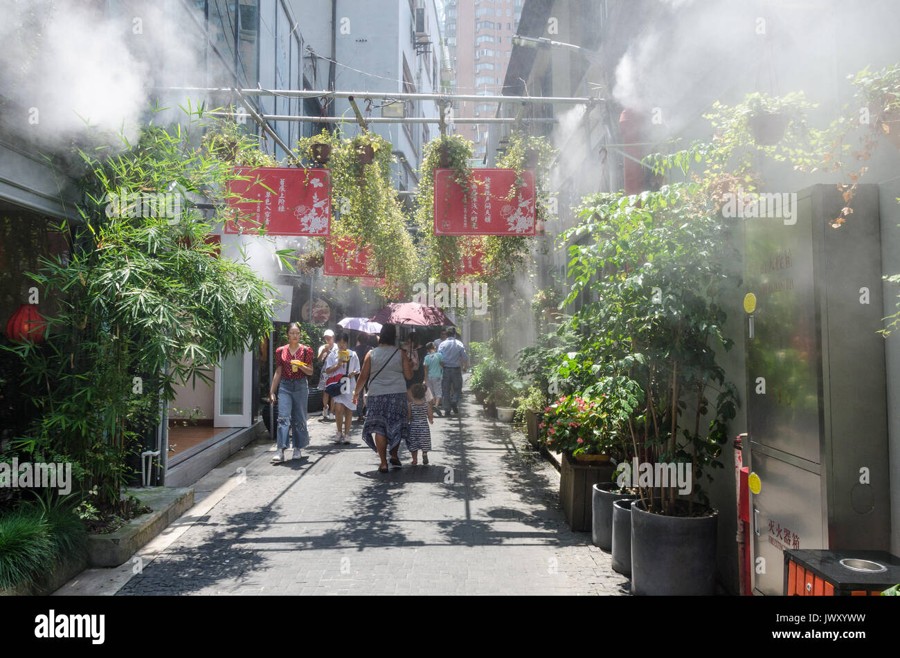 Tourists wander the streets of Tianzifang in Shanghai, China. A cooling system sprays a mist to bring relief from the hot sun. - Stock Image