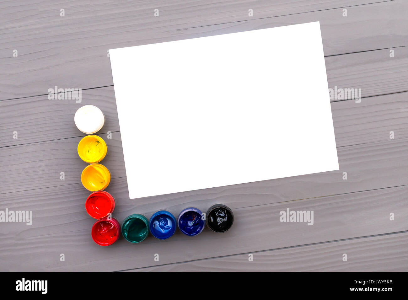 Colored paints and sheet of paper - Stock Image