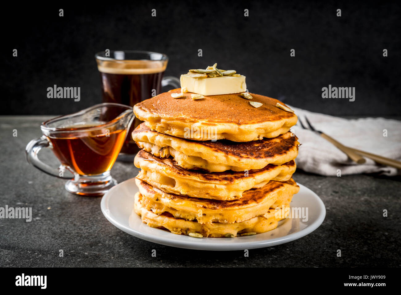Autumnal traditional food. Stack of pumpkin pancakes with butter, pumpkin seeds and maple syrup. With a cup of coffee. On a black stone table. Copy sp - Stock Image