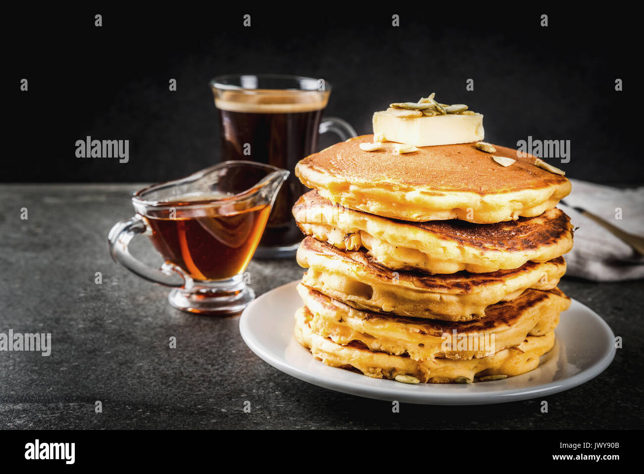 Autumnal traditional food. Stack of pumpkin pancakes with butter, pumpkin seeds and maple syrup. With a cup of coffee. Stock Photo